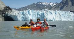 Kayakers in front of a glacier