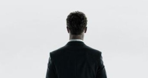 A man in a suit facing out of the window