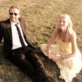 Gwyneth Paltrow and Chris Martin sit on grass
